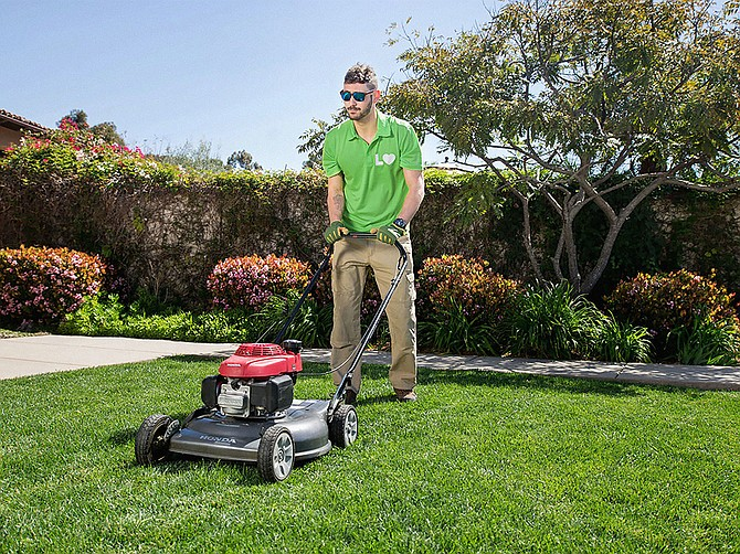 Photo courtesy of Lawn Love. A technician from startup Lawn Love mows a client's lawn in the 4S Ranch development of San Diego.