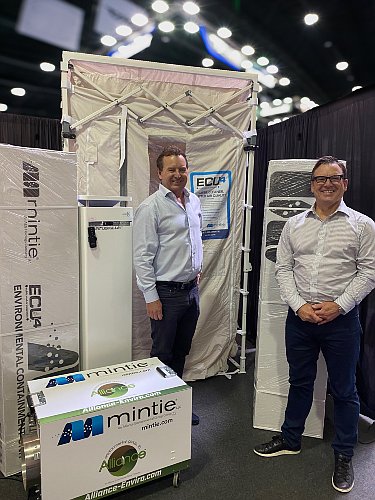 Mintie President Kevin Mintie (left) and Executive Vice President James Mintie with one of the company's containment units.